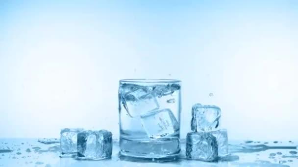 Eiswürfelspritzer im Wasserglas auf weißem Eis, Zeitlupe
