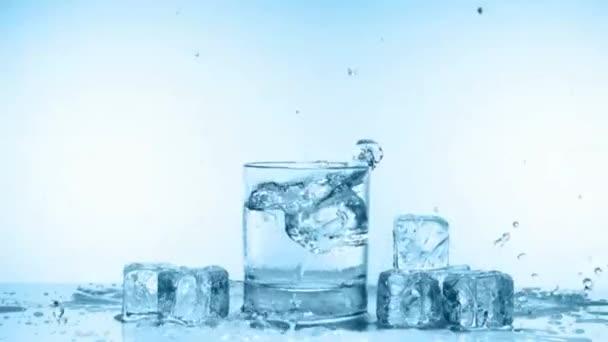 Ice cube splash pohár vizet a fehér, lassú mozgás
