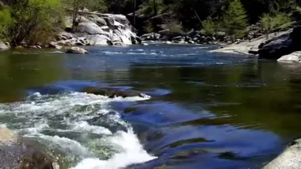 Clear mountain river water spills over rocks