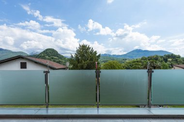 A glass parapet of a modern building balcony overlooking the Swiss hills