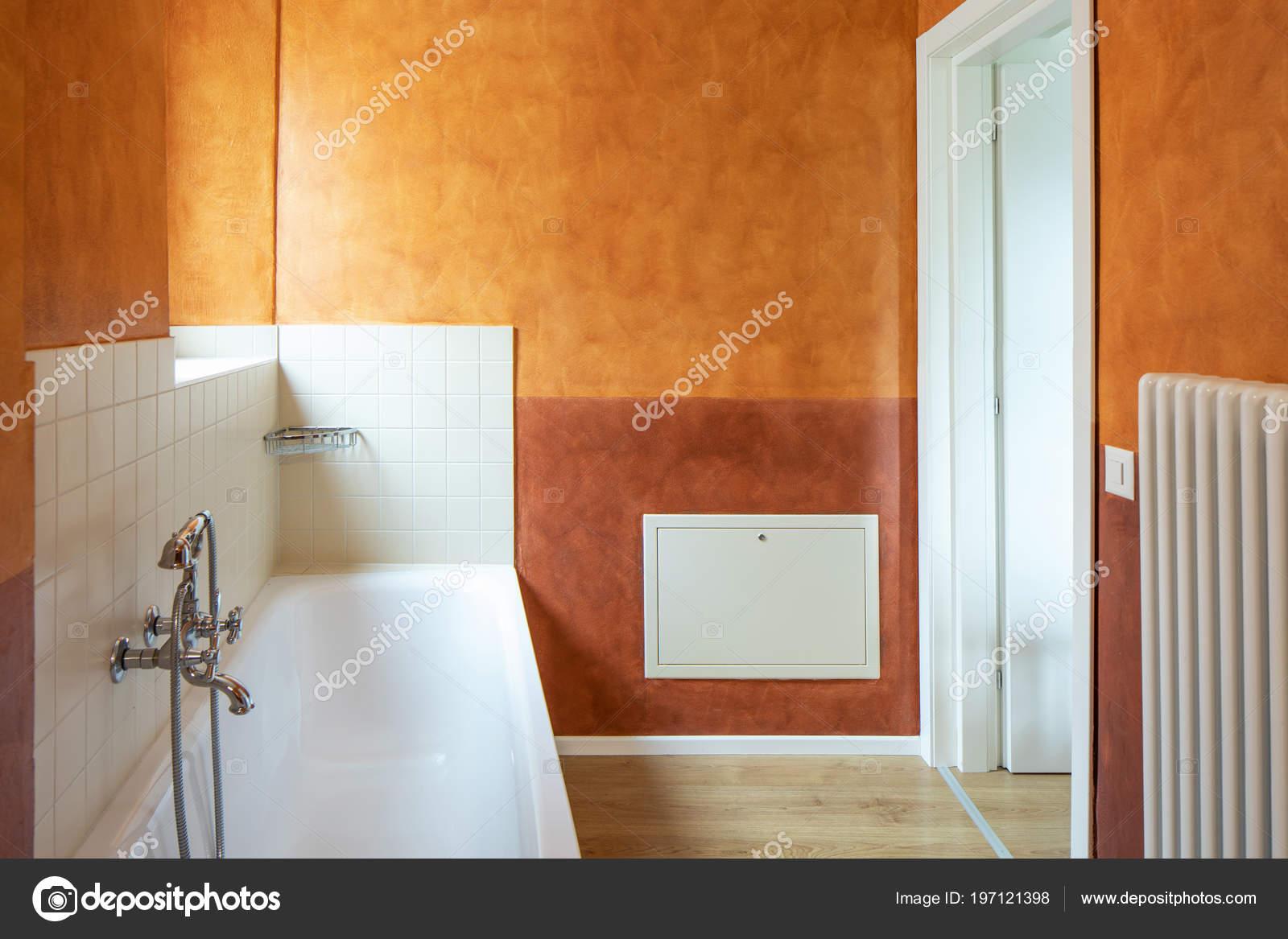 Bagno con finiture moderne pareti color arancio nessuno all