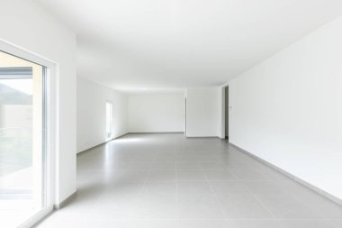 Large living room and completely white kitchen in a modern open space. Nobody inside