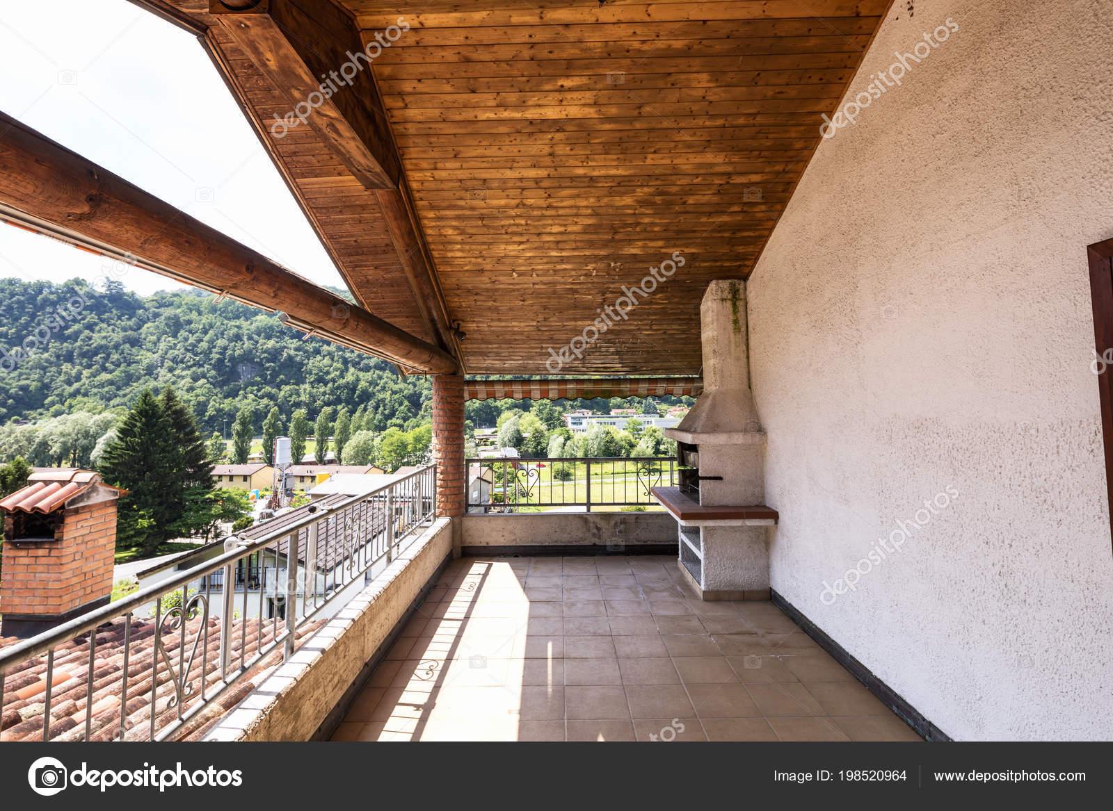 Terrazza con soffitto legno piastrelle paesaggio colline nessuno