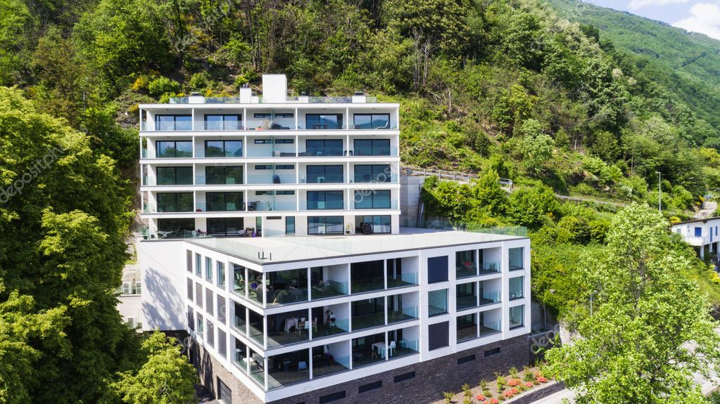 Modern house exterior with balconies and surrounded by the nature of Lake Maggiore. Nobody inside