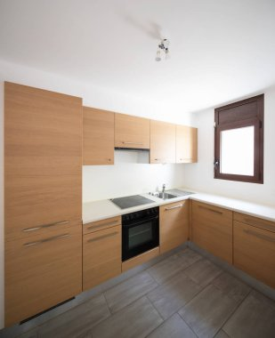 Modern kitchen in wood and white walls, small window. Nobody inside