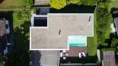 Vnější moderní bílá Vila s bazénem a zahradou, nikdo uvnitř. Letecký pohled shora