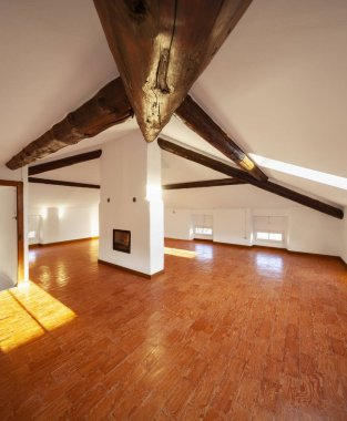 Attic with exposed wooden beams and a fireplace in the center of the room. Nobody inside