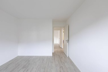 Empty room with white walls and open door on the right. Nobody inside