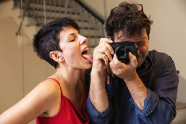 Young attractive woman licks a hairy arm of a photographer