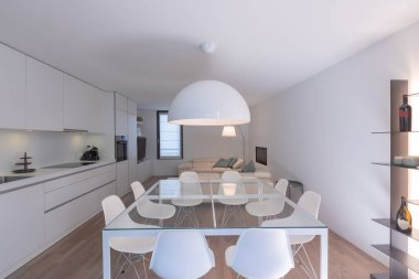 Large open space with glass table, designer chairs, white kitchen and comfortable leather sofas. White walls. Nobody inside