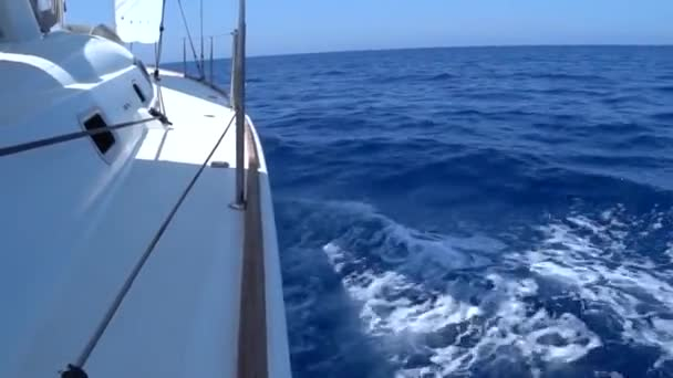 A view from the yachts deck to the bow and sails, close-up.S ide view with blue sea and waves.