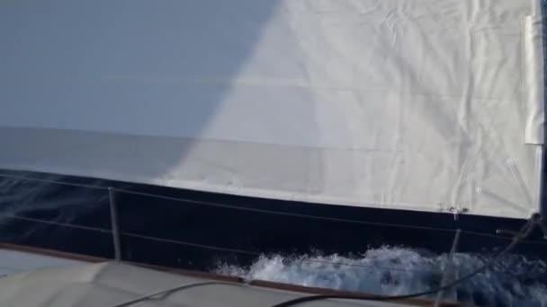 Pohled z paluby jachty na přídi a plachty, detail. S ide pohled s modrým mořem a vlny