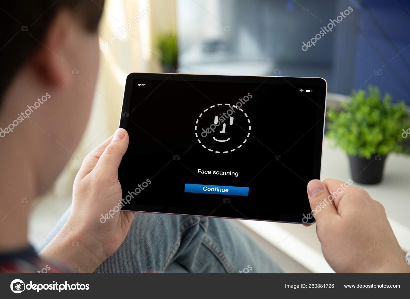 Man hands holding computer tablet with face ID scanning