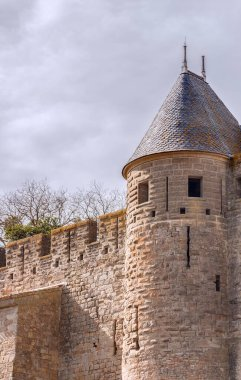 Battlement fortress wall with the round tower against the sky