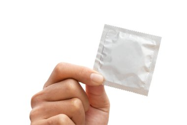 Man's hand holding condom isolated on a white background