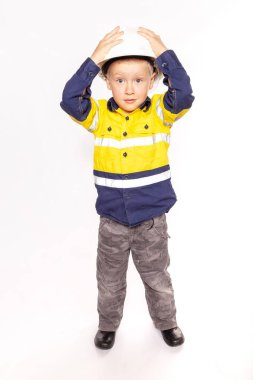 Young blond caucasian boy hands on hard hat with a shocked look role playing as a construction worker supervisor in a yellow and blue hi-viz shirt, boots.
