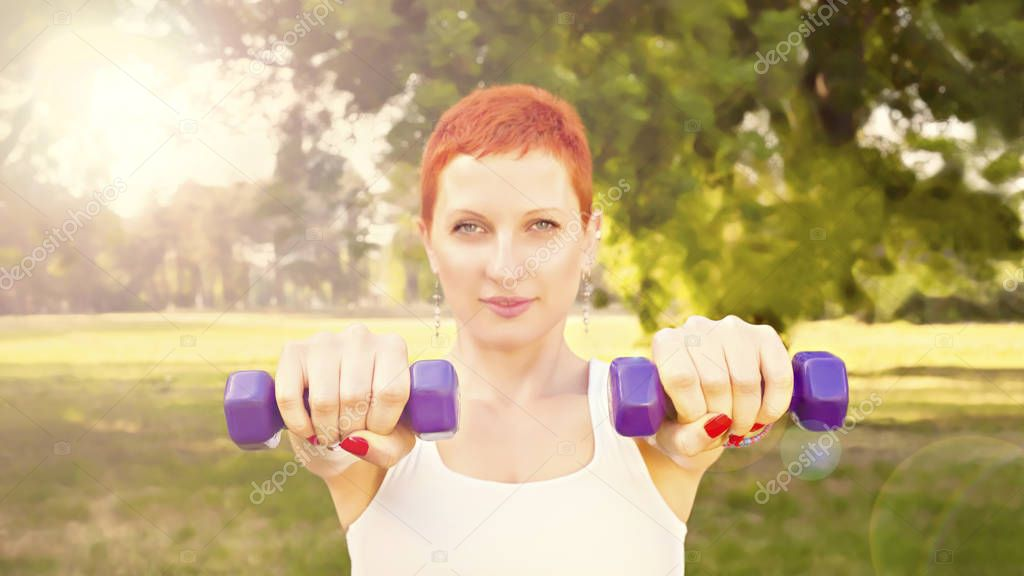 Portrait of cheerful young redhead woman in fitness wear exercising with dumbbells in park