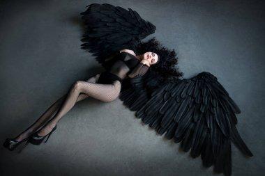 Sensual brunette woman posing in dark angel costume
