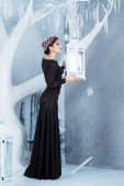 Fotografie Elegant woman in black dress and ruby crown posing in winter decorated interior