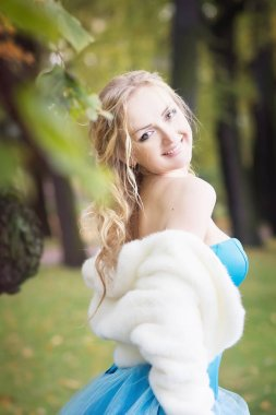 Portrait of young woman in blue fairy dress and white short fur coat in autumn park
