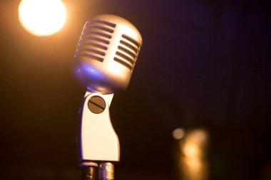 Close view of metal retro microphone in spotlights on dark background