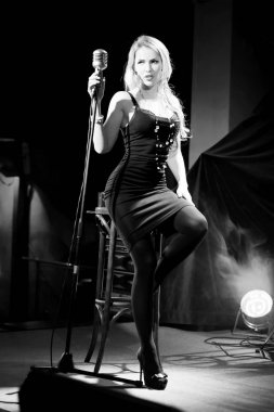 Gorgeous blonde woman in sensual dress singing on stage