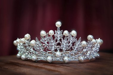 Elegant diamond diadem with pearls on wooden surface