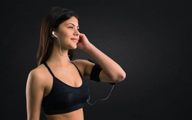 Young sport girl listening music on black background