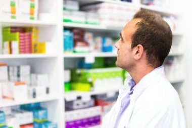 Adult man pharmacist in pharmacy looking for medications