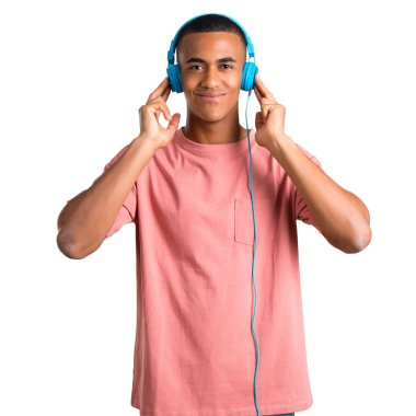 Young african american man listening to music with headphones on isolated white background