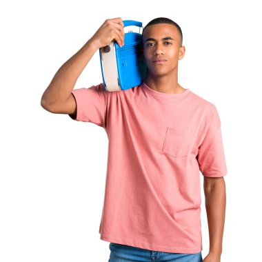Young african american man holding a blue vintage radio on isolated white background