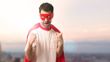 Superhero man with mask and red cape celebrating a victory and happy for having won a prize on a sunset background