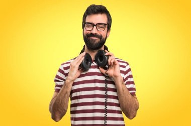 Happy Man with glasses listening music on colorful background
