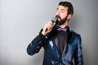 Handsome man with sequin jacket singing with microphone on grey background