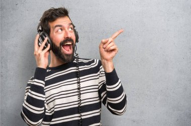Happy Man with beard listening music on textured background