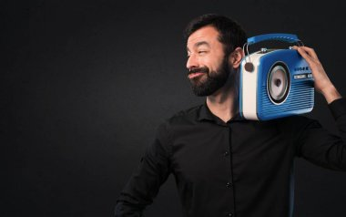 Handsome man with beard holding a radio on black background