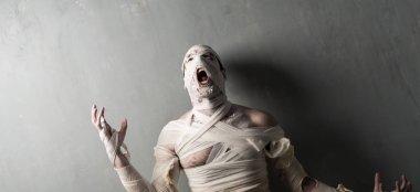 Terrorific mummy screaming on textured wall background.  Halloween holidays