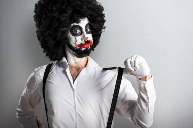 Killer clown with knife proud of himself on textured background