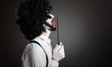 Killer clown with knife on textured background