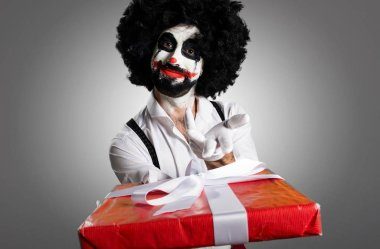Killer clown holding a gift on textured background