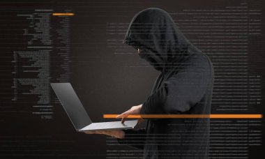 Hacker with his computer on dark background