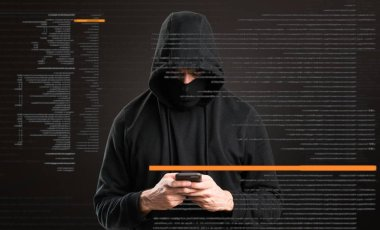 Hacker with his mobile on dark background
