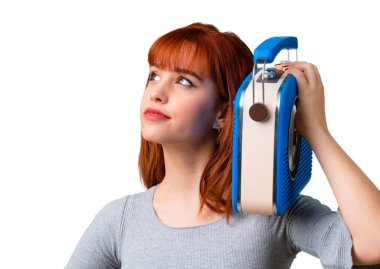 Young redhead girl holding a blue vintage radio
