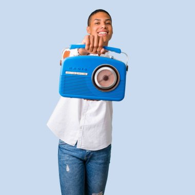 Young african american man with white shirt holding a blue vintage radio on isolated blue background