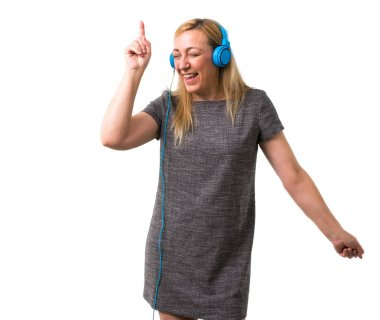 Middle-age blonde woman listening to music with headphones and dancing on isolated white background