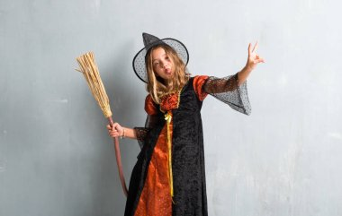 Little girl dressed as a witch and holding a broom for halloween holidays making victory gesture