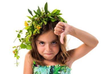Cute girl with crown of flowers doing bad signal