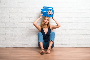 Blonde girl sitting on the floor holding a radio