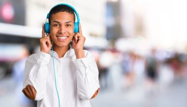 Young african american man with white shirt listening to music with headphones in the middle of the city