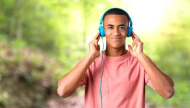 Young african american man listening to music with headphones in a park